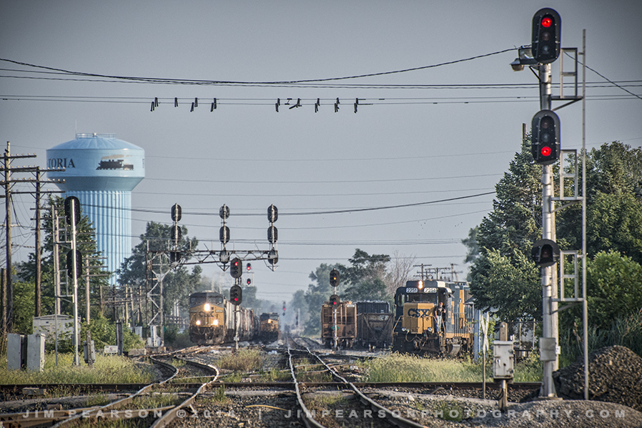 "August 7, 2014 - Looking south toward the diamond at ""F"" Tower in the ""Iron Triangle"" at Fostoria, Ohio as trains work in yard."