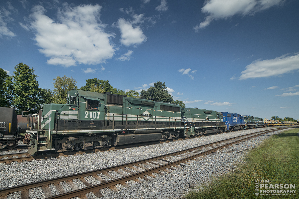 August 21, 2015 – Paducah and Louisville Railway's 2107 heads northbound pulling a southbound military train, at Calvert City, Ky with Natchez Railway's 2602 as it's third unit. ?- Tech Info: 1/1000sec, f/13, ISO 720, Lens: Rokinon 14mm on a Nikon D800 shot and processed in RAW.