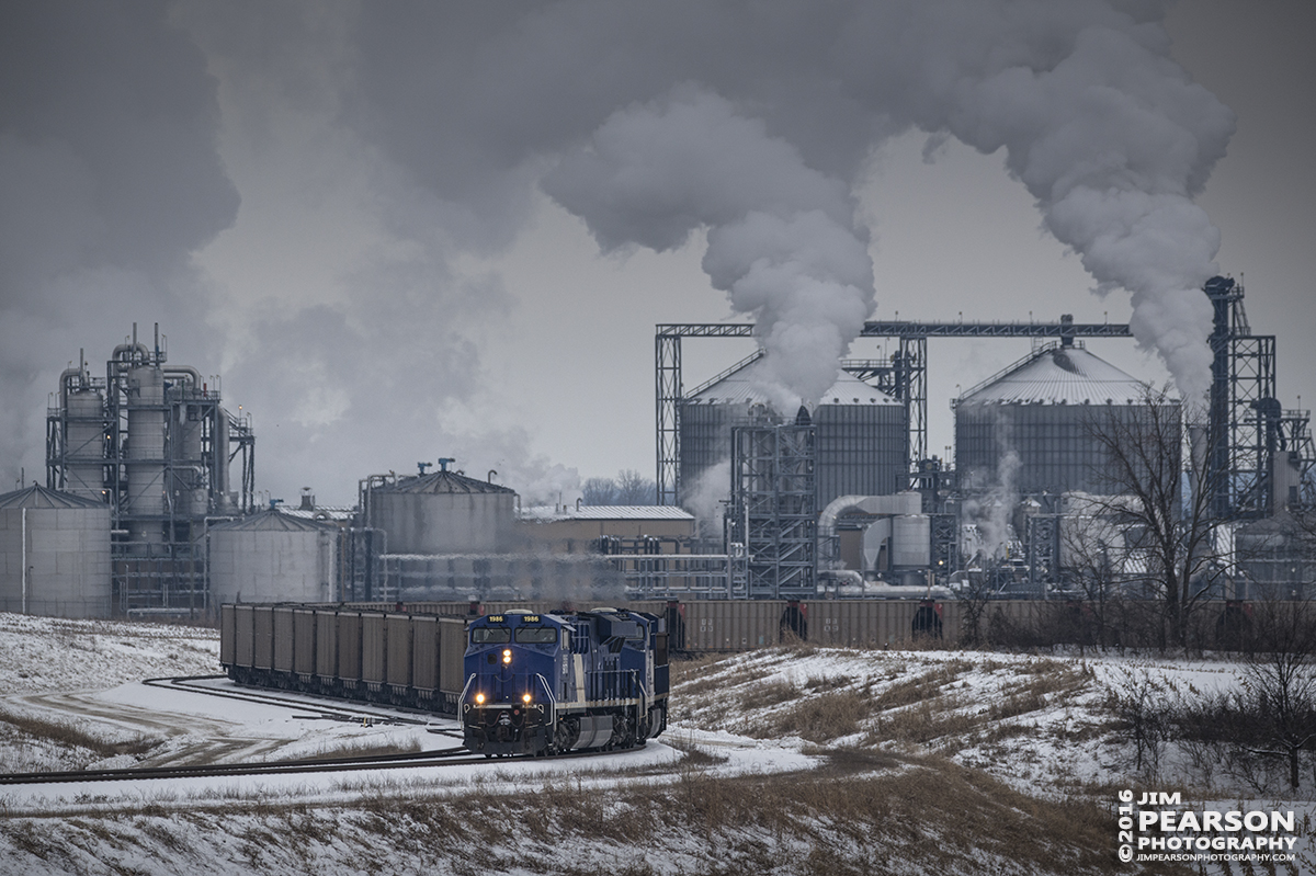 January 20, 2016 - Evansville Western Railway's SS1 pulls away from the Sitran Dock with a empty coal train with lease units SVTX 1986 and 1982 as power, at West Franklin, Indiana on a cold wintery day. In the background putting out all the steam is the Abengoa Bioenergy plant.  - Tech Info: 1/1250 | f/6.3 | ISO 400 | Lens: Sigma 150-600 @ 310mm with a Nikon D800 shot and processed in RAW.