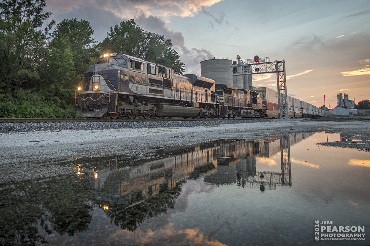 August 20, 2016 - Norfolk Southern Wabash Heritage Unit, 1070, is reflected in standing water, as it makes its way east into the yard at Princeton, Indiana on NS 223 with a loaded intermodal at sunset.