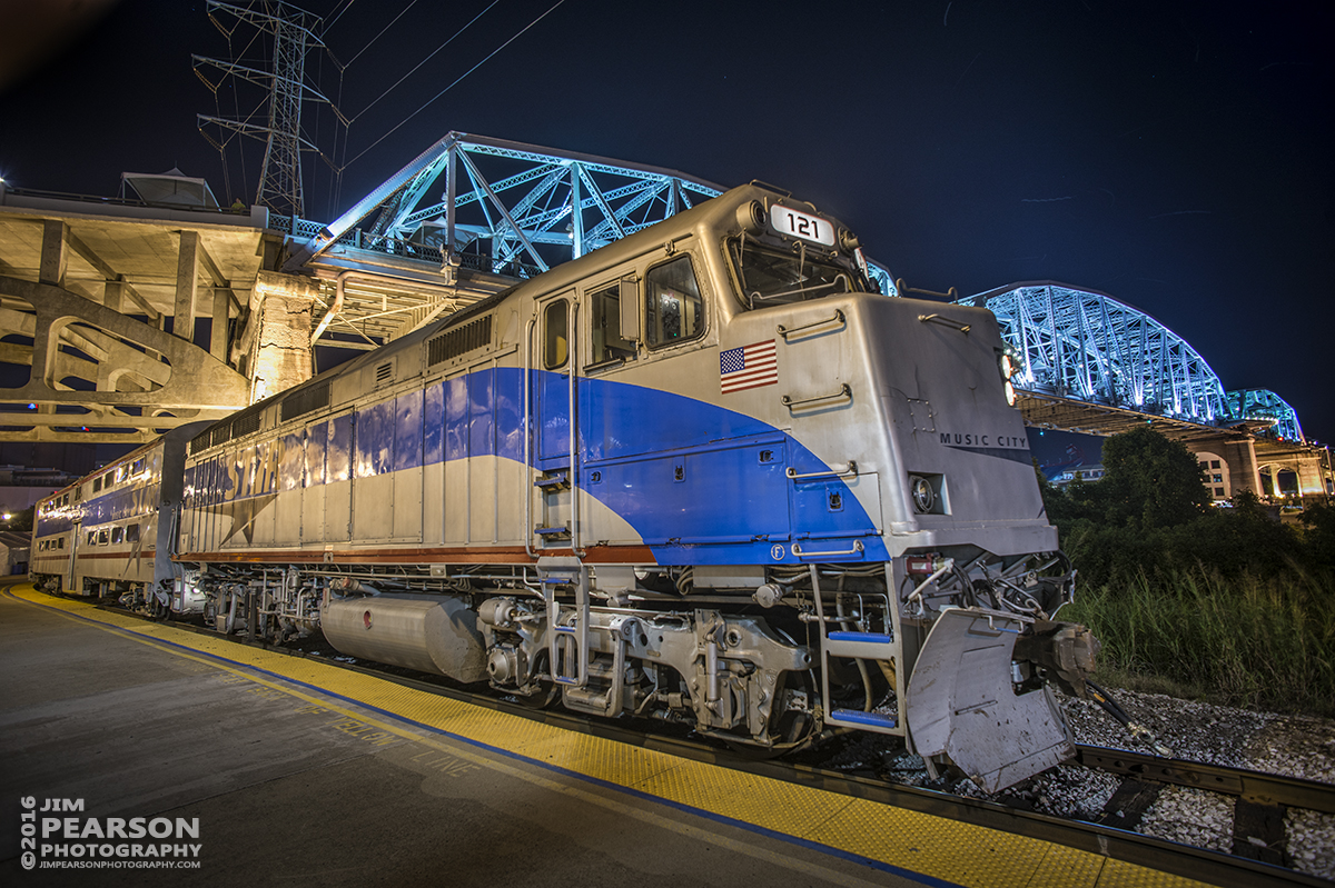September 9, 2016 - A Music City Star commuter train with engine 121 (F40PH), sits along the river front in downtown Nashville, Tennessee, with the John Seigenthaler Pedestrian Bridge lit-up in the background.
